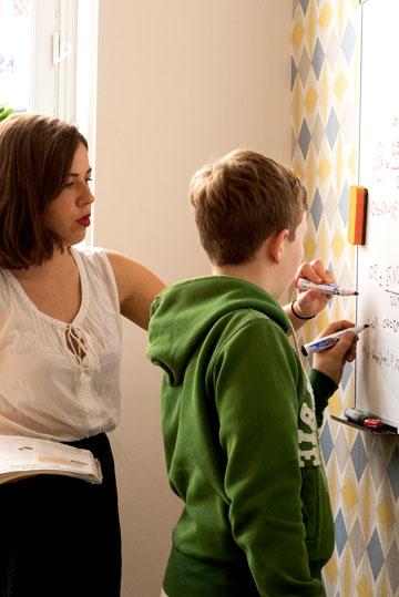 Tuteur d'espagnol aidant un élève au tableau